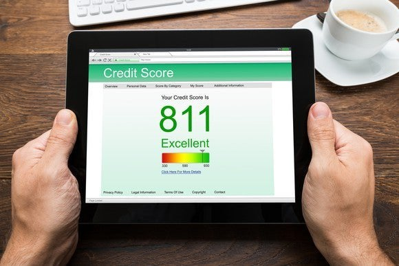 Hands holding tablet show 811 credit score