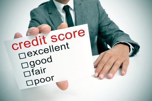 Businessman holding card that says credit score, with categories ranging from excellent to poor.