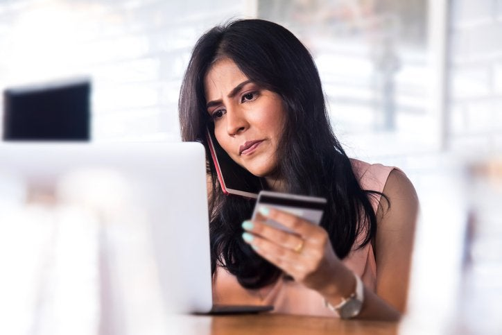 A concerned woman at a laptop holding a credit card