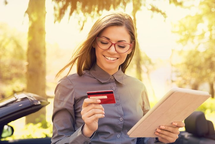 A smiling woman with a credit card.