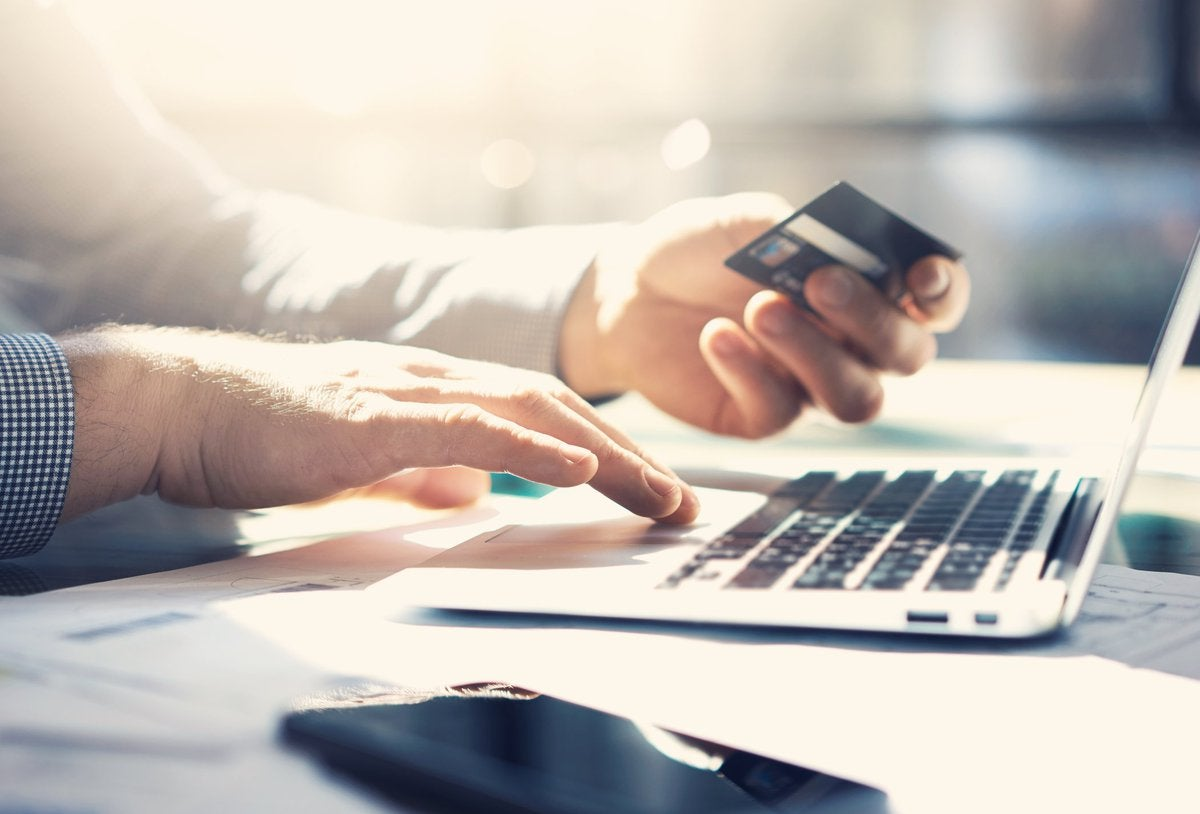 Man using a laptop and holding a credit card.