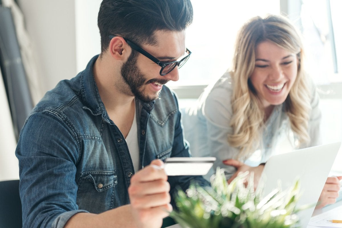 A young man and woman use a credit card while shopping on a laptop.