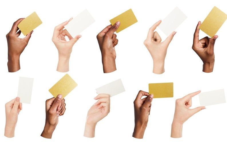 Various hands holding credit-card-sized nondescript note cards.