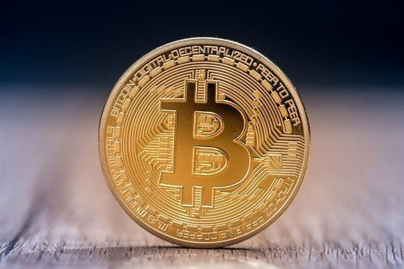 A physical gold coin marked with the Bitcoin B.