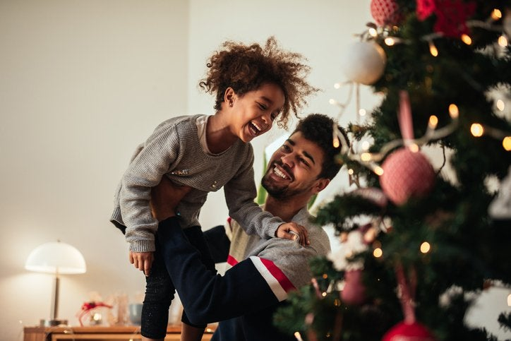 A smiling dad holding up his laughing daughter while they decorate a Christmas tree.