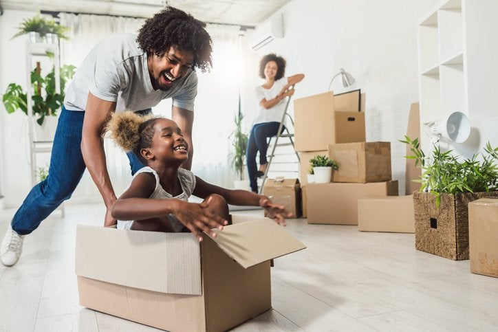 A dad pushing his laughing daughter along the floor in a moving box while the mom looks on smiling while packing other boxes.