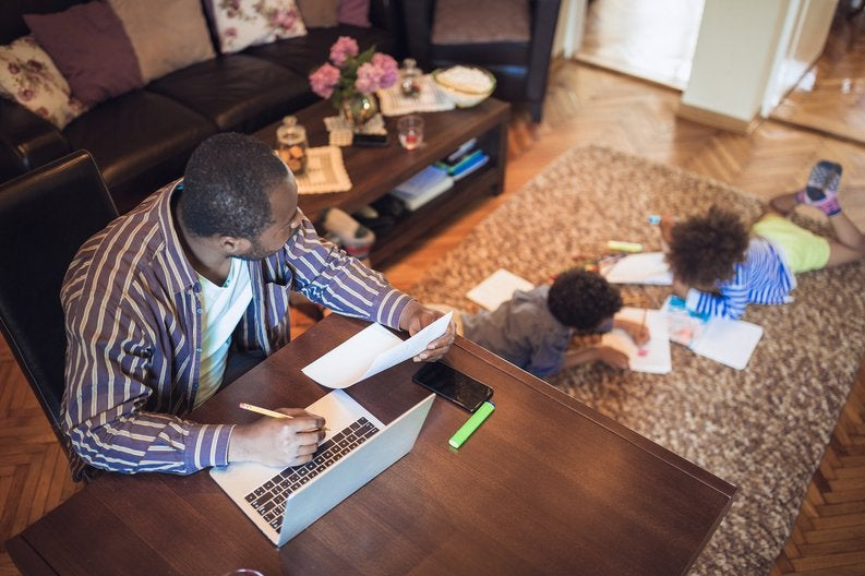 A father working at a table and watching his kids do homework on the floor of the living room.