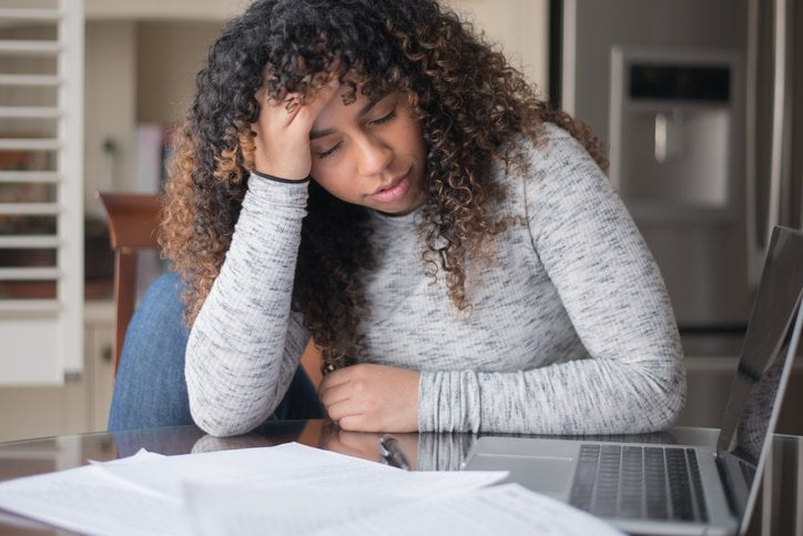 A woman looking worried, at a table with papers and a laptop.