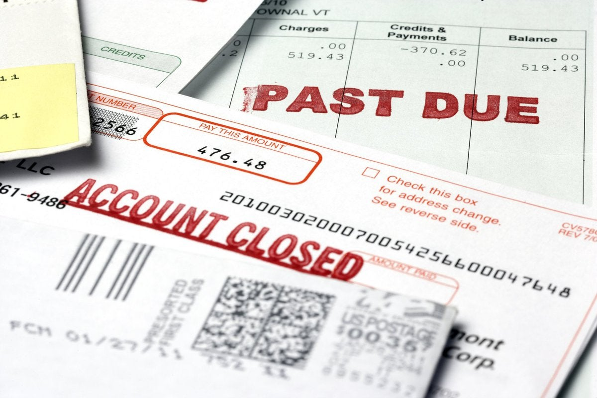"""Financial paperwork including a bill labeled """"Past Due"""" and another labeled """"Account Closed"""""""