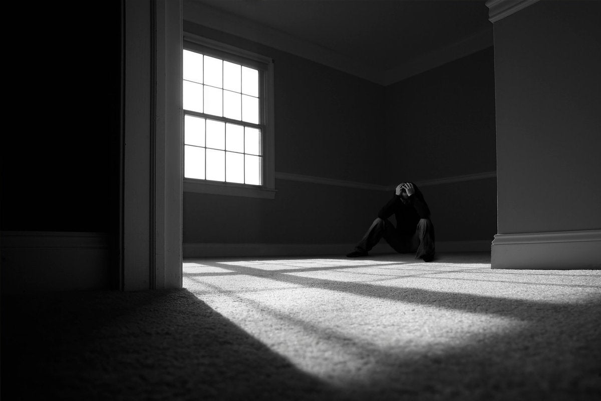 A person sitting in the corner of a dark room holding their head in their hands.