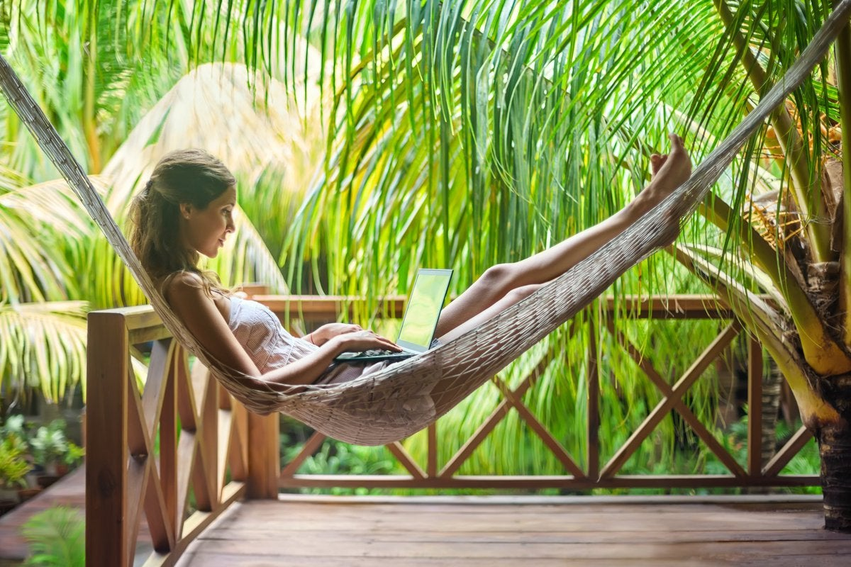 digital nomad using a laptop in a hammock surrounded by palm trees -- vacation remote work