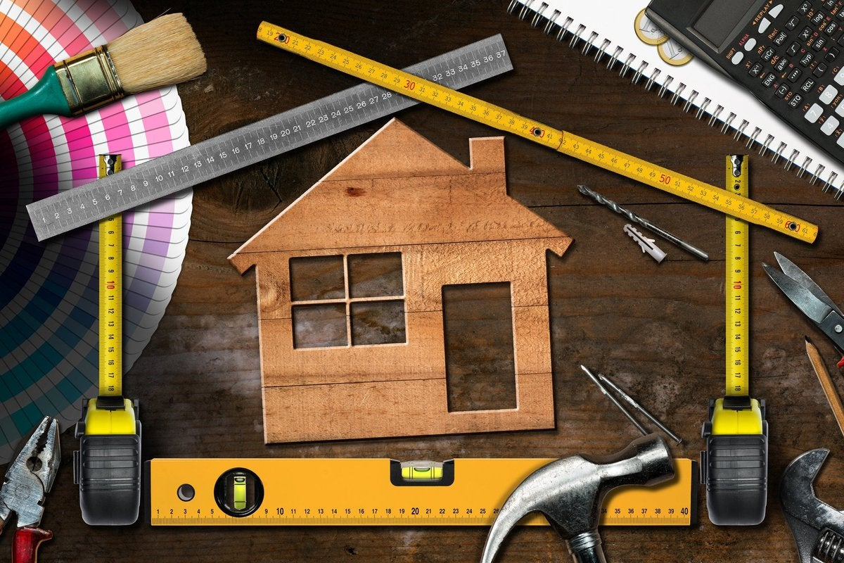 Wooden cutout of house surrounded by home improvement tools.