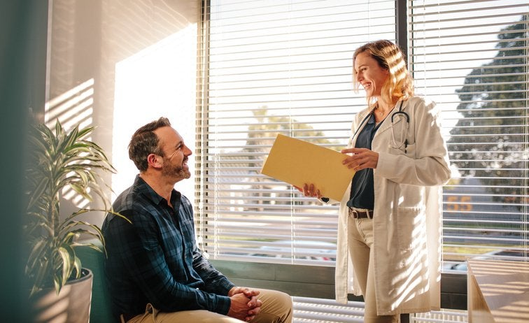 A doctor standing in front of a sunny window in her office and speaking with her male patient sitting in a chair.