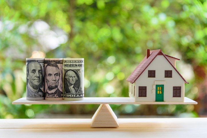 Dollars on a scale, balanced against a house.