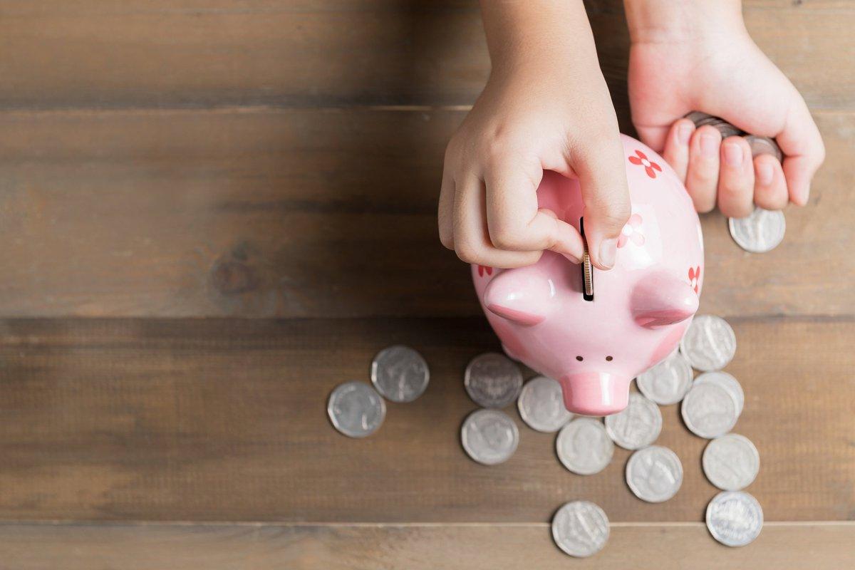 Han dropping coins into a piggy bank.
