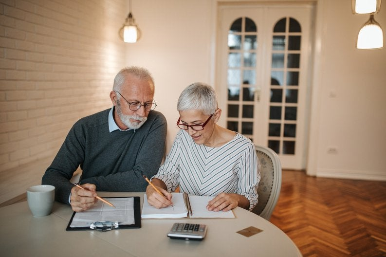 elderly couple with notebook and calculator