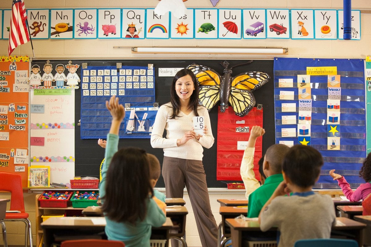A smiling teacher standing at the front of an elementary school classroom while students raise their hands.