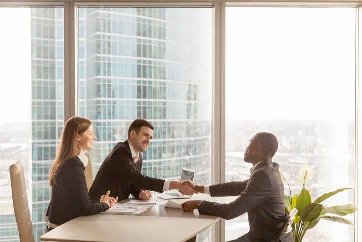 An employee shaking hands with his two bosses across a desk in a sunny high-rise office.