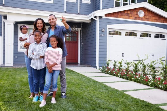 African-American family standing outside of a new home holding keys
