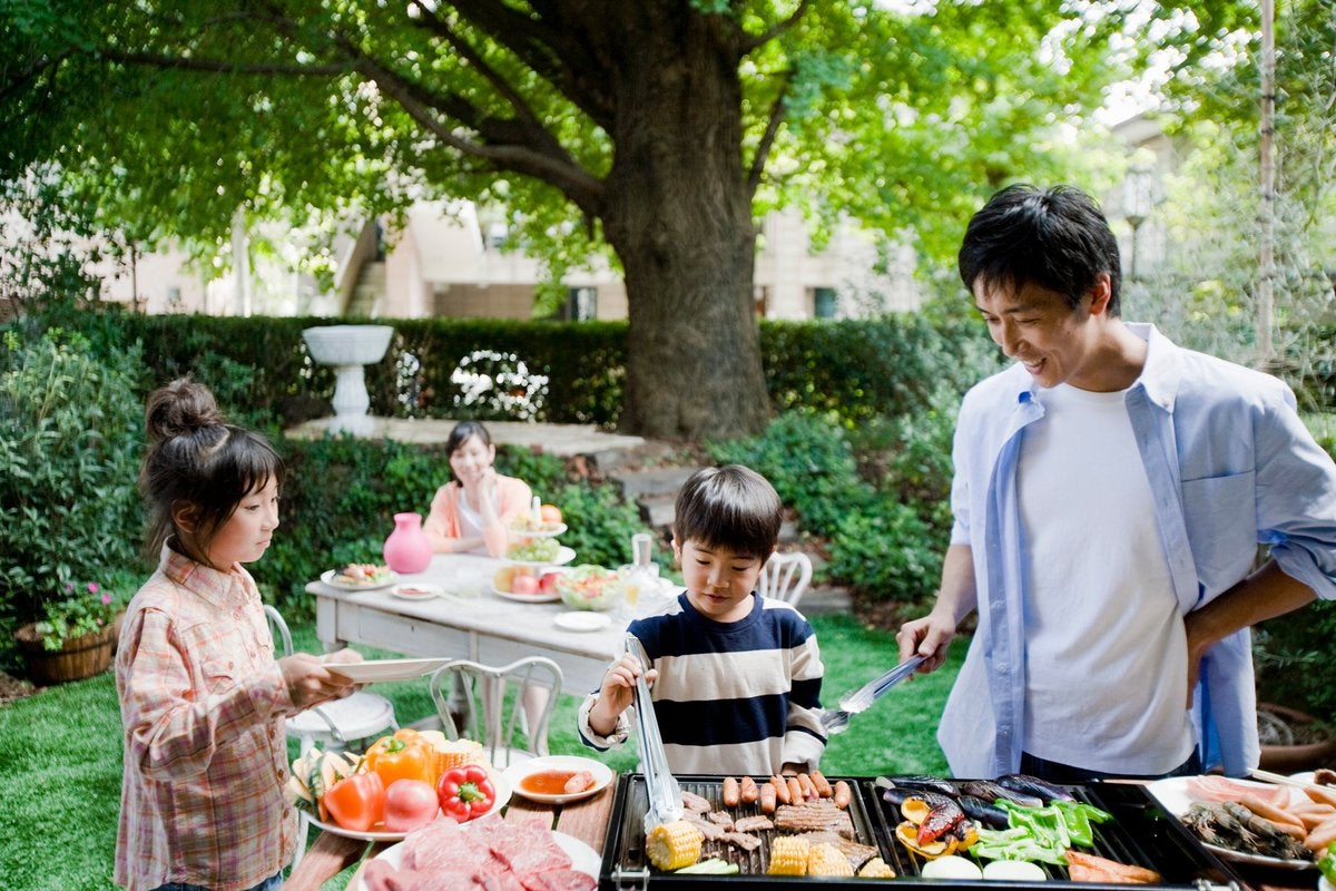 Two parents and two kids enjoying a backyard barbecue surrounded by green trees.