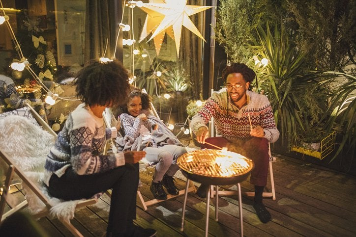Two parents and their child making smores on their backyard patio decorated with twinkle lights.