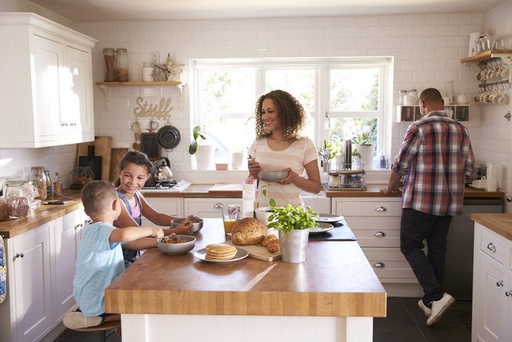 A mom and dad preparing breakfast for their young daughter and son while they sit at the kitchen island.