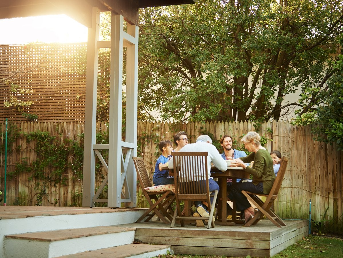 A family eating a meal at a patio table on their back deck.