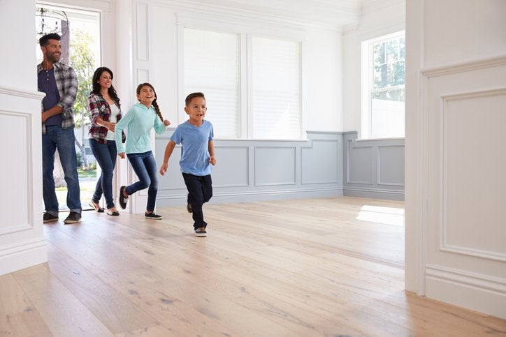 A family with young children running into the empty foyer of their new home.