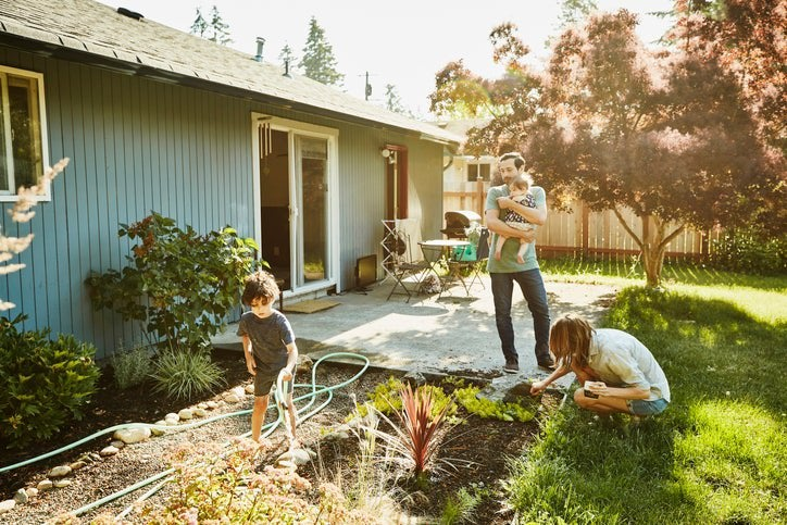 A mom working in the backyard garden with a toddler while the dad walks out of the house holding a baby.