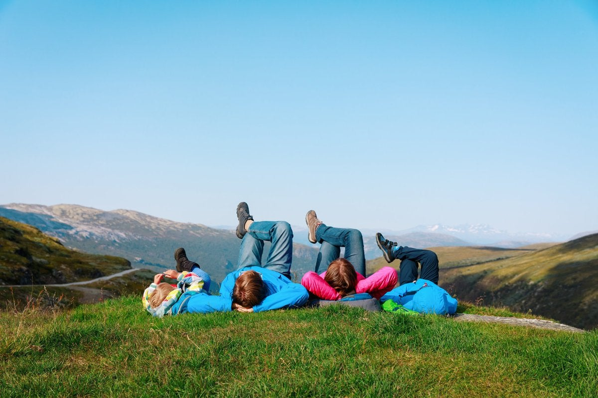 family of four lying on a grassy hill in Norway.