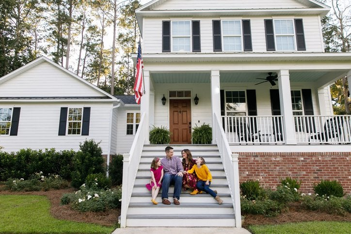 A couple with two kids on the front steps of a house.