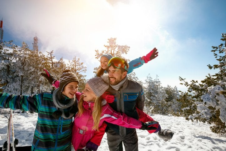 A mom, dad, son, and daughter taking a break from downhill skiing to play in the snow on a sunny mountain slope surrounded by trees.