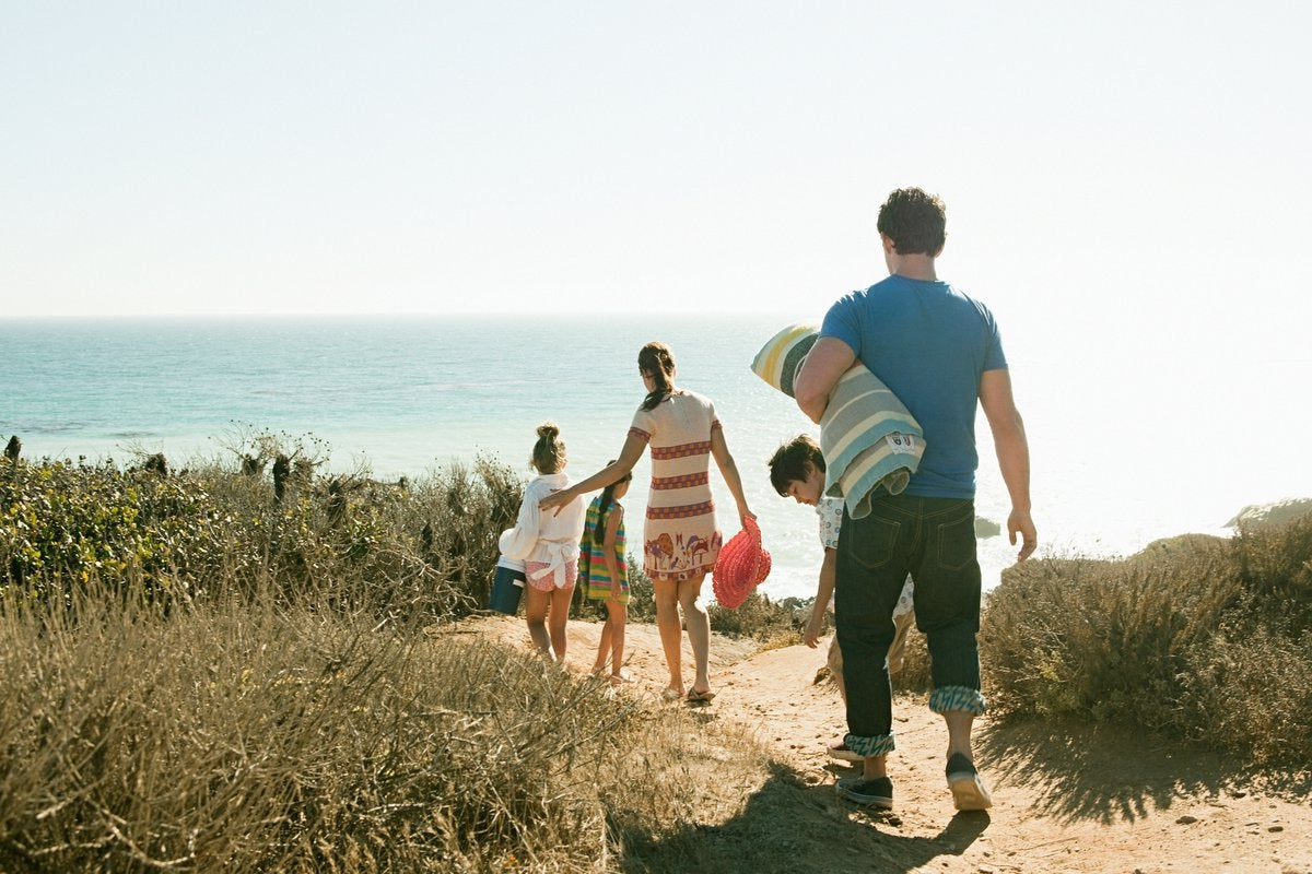 Two parents and three children carrying towels and walking to the beach.