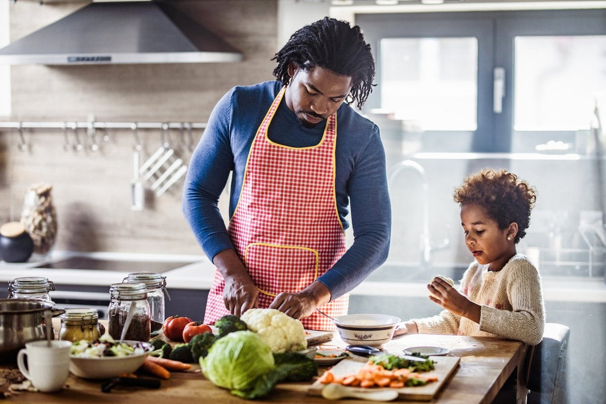 A father and young daughter cooking a meal together in the kitchen.