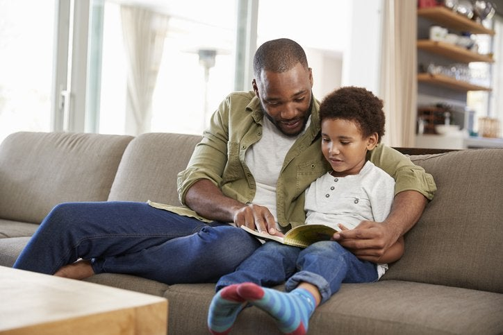 A father sitting on a couch with his arm around his son while they read a book.