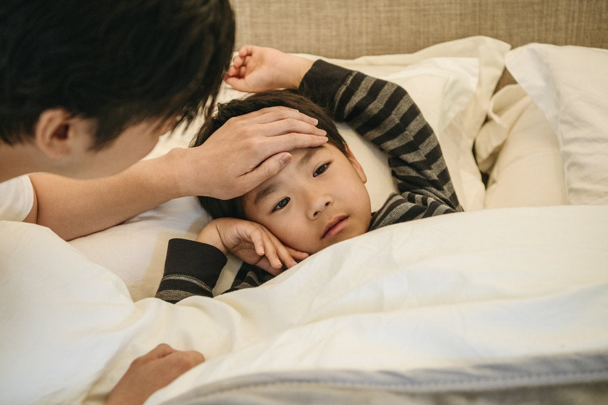 A child in bed with his dad's hand on his forehead to check his temperature.