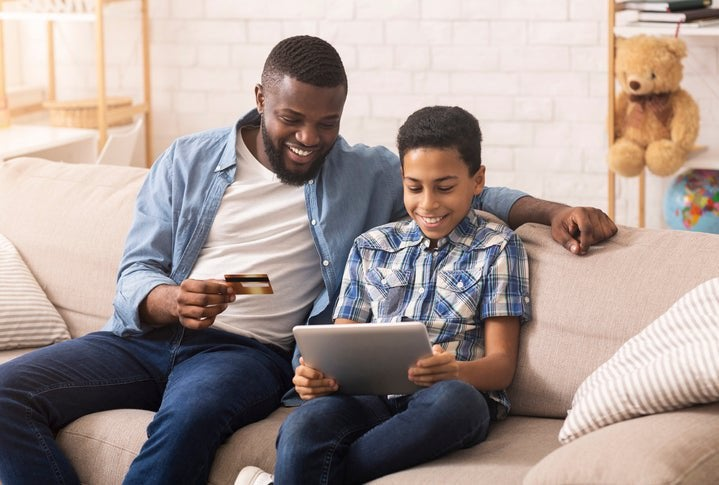 A father and son looking at a laptop and a credit card.