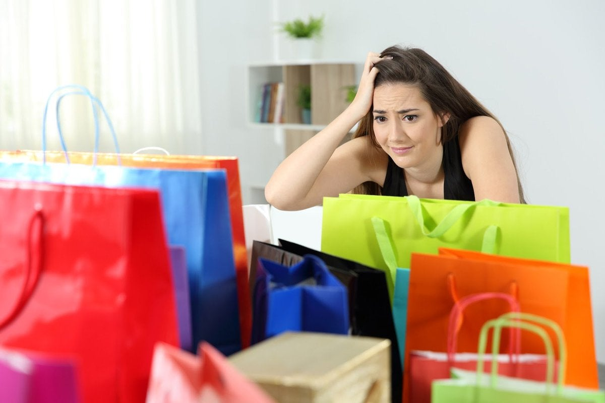 A woman with a concerned look on her face sits looking at a bunch of shopping bags.