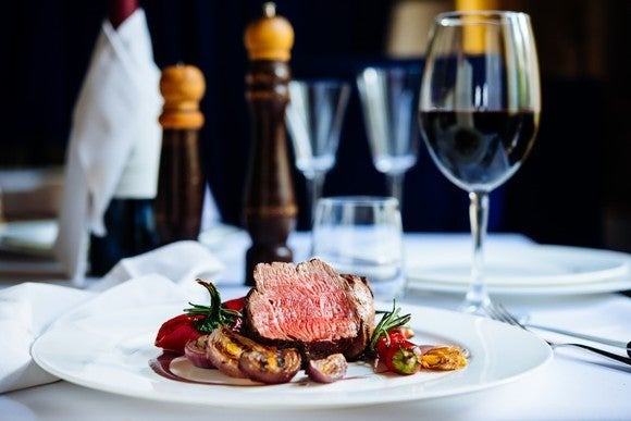 Fine dining restaurant with steak dinner and glass of red wine.