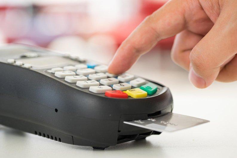 finger typing number into credit card reader