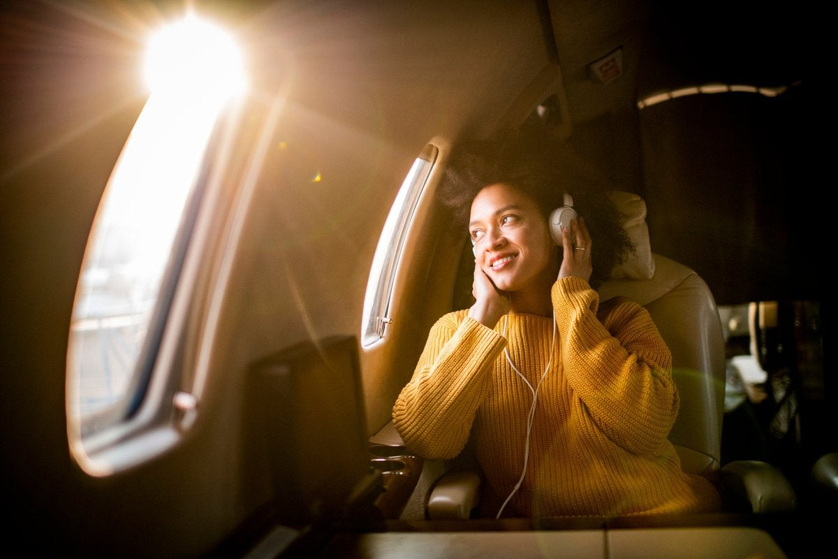 A smiling airplane passenger listening to music and looking out the window.