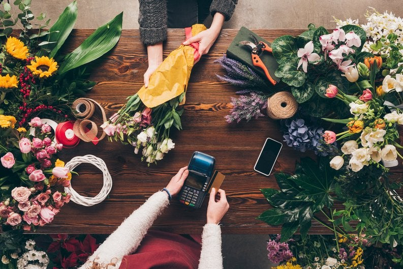 A florist swiping a credit card between bunches of flowers.