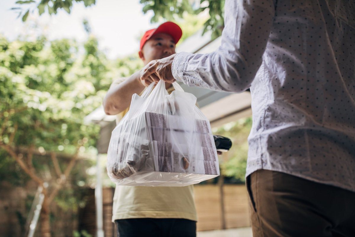 A delivery man handing over a bag of takeout food to a customer.
