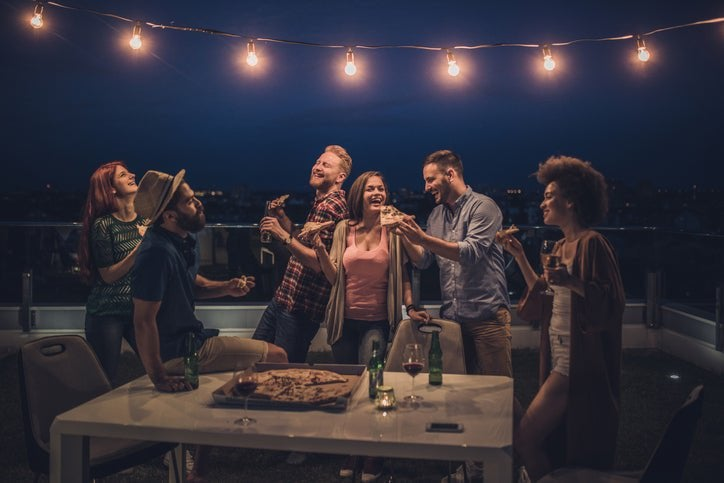 A group of laughing friends sharing pizza and beers on a rooftop at night under decorative string lights.