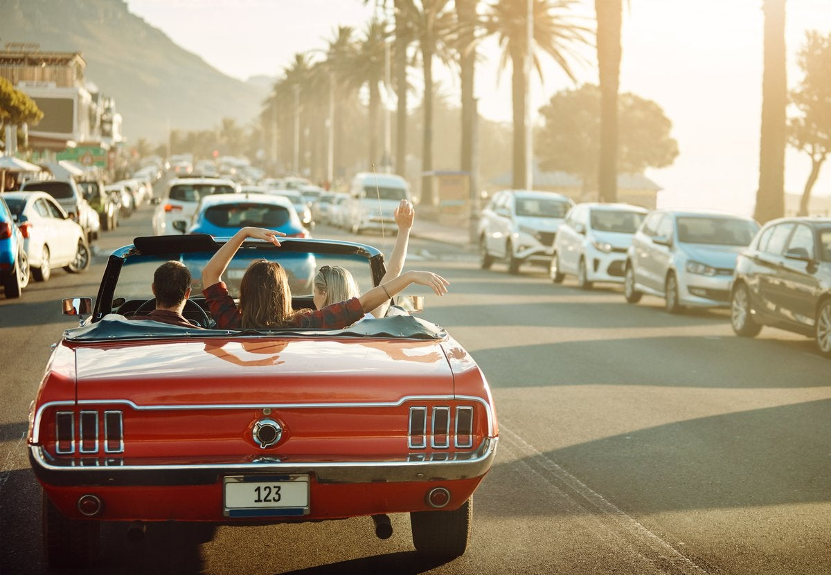 Three friends driving down a sunny beachside road in a red convertible.