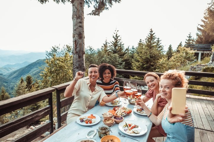 Four smiling women taking a selfie while dining on a mountainside deck at a restaurant.