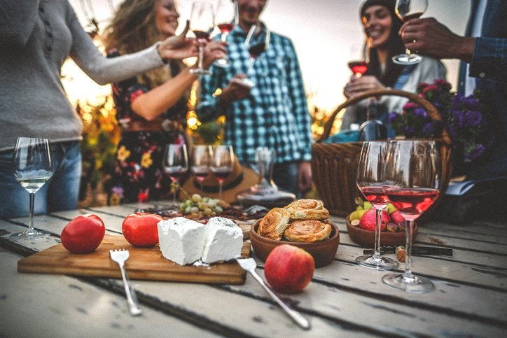 A group of friends drinking wine around a cheese plate on a picnic table in a vineyard.