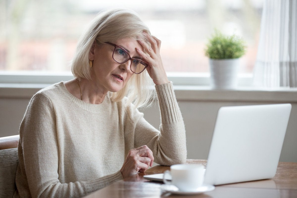 Senior woman looking at laptop with frustrated expression