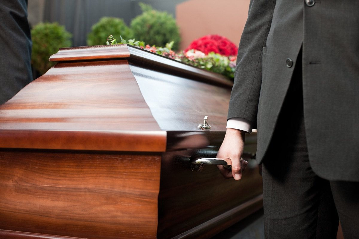 Casket being carried by men in suits.