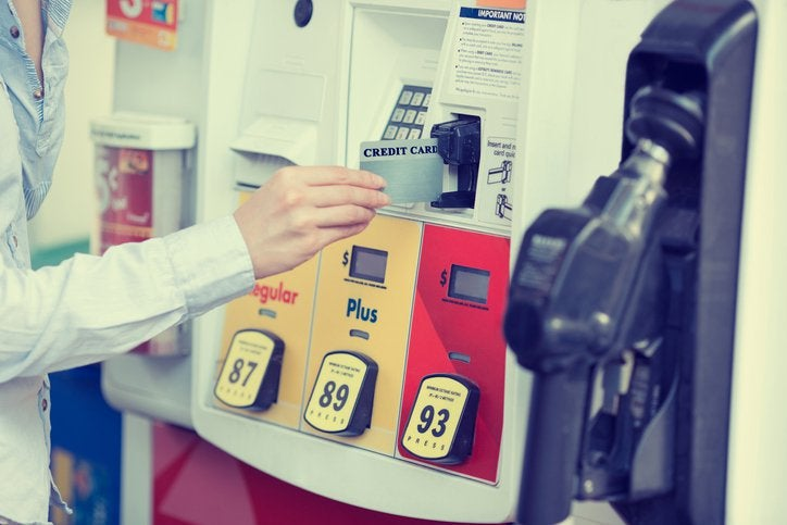 A hand placing a credit card into a gas pump card reader.